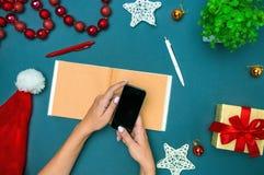 Las manos del famale con las decoraciones de la Navidad Fotografía de archivo