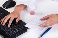 Las manos del farmacéutico que mecanografían en el teclado Fotografía de archivo libre de regalías