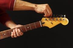 Las manos del guitarrista adaptan la guitarra eléctrica en fondo negro Foto de archivo libre de regalías