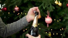 Las manos del hombre abren la botella de champán en el fondo adornado del árbol de navidad, concepto de la celebración del Año Nu almacen de video