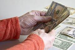 Las manos del hombre caucásico que cuentan billetes de banco del dólar fotos de archivo libres de regalías