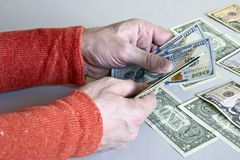 Las manos del hombre caucásico que cuentan billetes de banco del dólar foto de archivo libre de regalías