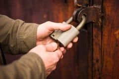 Las manos del hombre cierran la cerradura, desbloqueando un candado foto de archivo libre de regalías