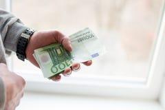 Las manos del hombre con euro en el fondo blanco Concepto financiero del negocio foto de archivo