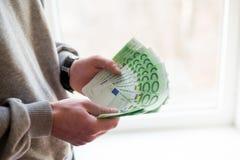 Las manos del hombre con euro en el fondo blanco Concepto financiero del negocio imagen de archivo