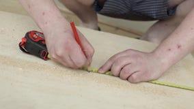 Las manos del hombre con la regla amarilla y el lápiz rojo que hacen marcas en tablón de madera almacen de metraje de vídeo