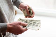 Las manos del hombre con los dólares en el fondo blanco el hombre da un soborno fondo de la corrupción imagen de archivo