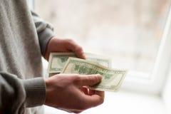 Las manos del hombre con los dólares en el fondo blanco el hombre da un soborno fondo de la corrupción fotos de archivo