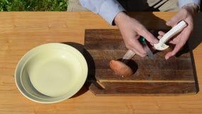 Las manos del hombre cortaron setas rojas del casquillo de la rebanada con la tabla de madera del cuchillo metrajes