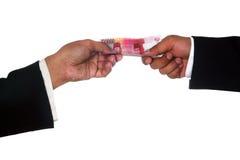 Las manos del hombre dan el dinero a la otra mano del hombre fotografía de archivo libre de regalías