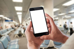 Las manos del hombre de negocios celebran la pantalla en blanco móvil del teléfono elegante en el aeropuerto Fotos de archivo libres de regalías