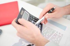 Las manos del hombre de negocios con la calculadora Imagen de archivo libre de regalías