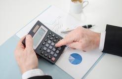 Las manos del hombre de negocios con la calculadora Fotografía de archivo libre de regalías