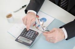 Las manos del hombre de negocios con la calculadora Imagenes de archivo
