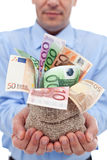 Las manos del hombre de negocios con los billetes de banco euro en un dinero empaquetan Foto de archivo libre de regalías