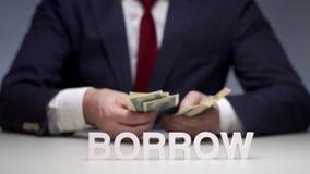 Las manos del hombre de negocios consideran el billete de banco de un paquete de dinero para que el préstamo partner almacen de video