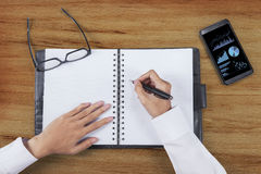 Las manos del hombre de negocios escriben el informe de negocios Fotos de archivo libres de regalías