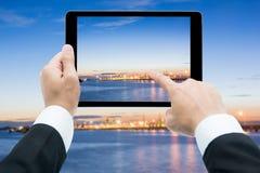 Las manos del hombre de negocios hacen tabletas tomar a imágenes muelles comerciales en el sol Imagen de archivo libre de regalías