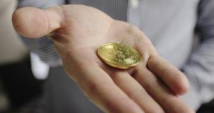 Las manos del hombre de negocios muestran las monedas de Bitcoin BTC almacen de video