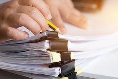 Las manos del hombre de negocios que buscan las pilas de documentos inacabadas de ficheros de papel en el escritorio de oficina p imágenes de archivo libres de regalías