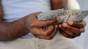 Las manos del hombre de negocios que cuentan nuevos cientos billetes de dólar almacen de metraje de vídeo