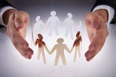 Las manos del hombre de negocios que protegen al equipo de gente de papel en el escritorio Imagen de archivo