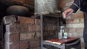 Las manos del hombre del aldeano llenan el vidrio de alcohol ilegal hecho hogar 4K almacen de video