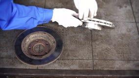 Las manos del hombre del mecánico comparan el disco de freno llevado viejo con el nuevo objeto metrajes