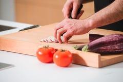 Las manos del hombre del primer que cortan verduras en una cocina imagen de archivo