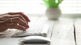 Las manos del hombre en el teclado de la PC con el ratón en primero plano almacen de metraje de vídeo