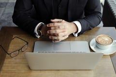 Las manos del hombre en la tabla con el ordenador portátil, el teléfono, el café y vidrios foto de archivo