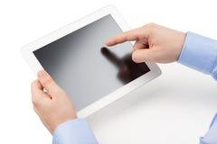 Las manos del hombre están llevando a cabo un ordenador y puntos de la tableta un finger en Imagen de archivo