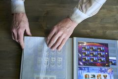 Las manos del hombre mayor sostienen el álbum de sello con la colección de los sellos, tema del espacio, fondo de madera imagen de archivo
