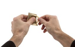 Las manos del hombre que abren el condón Imagenes de archivo