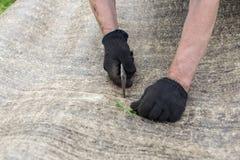 Las manos del hombre que cortan el material de techumbre Ruberoid Condtruction foto de archivo