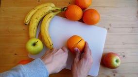 Las manos del hombre que cortan la naranja con el cuchillo en la tajadera