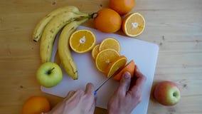 Las manos del hombre que cortan la naranja con el cuchillo en la tajadera almacen de metraje de vídeo