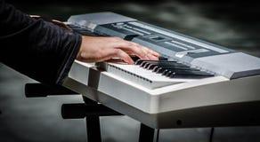 Las manos del hombre que juegan el piano del teclado son un instrumento musical electrónico imágenes de archivo libres de regalías