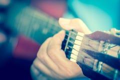 Las manos del hombre que juegan la guitarra acústica, el cierre para arriba, el vintage y el blurr Imagen de archivo libre de regalías