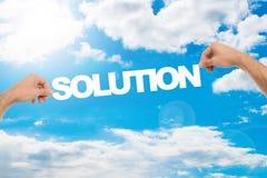 Las manos del hombre que llevan a cabo la solución contra el cielo azul nublado imagen de archivo