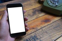 Las manos del hombre que sostienen el teléfono elegante con la pantalla en blanco del espacio de la copia Fotografía de archivo