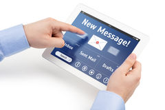 Las manos del hombre que sostienen una tableta con el interfaz del correo Imagen de archivo