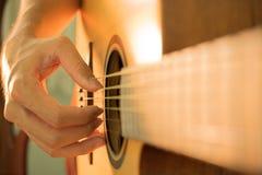 Las manos del hombre que tocan la guitarra acústica Imagen de archivo libre de regalías