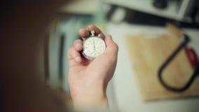 Las manos del hombre se sostienen y botón del cronómetro redondo viejo metrajes
