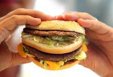 Las manos del hombre, sosteniéndose sobre una hamburguesa Fotografía de archivo