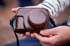Las manos del hombre sostienen la cámara en un caso de cuero elegante y elegante Imagen de archivo libre de regalías