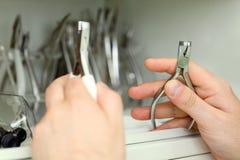 Las manos del hombre sostuvieron los instrumentos dentales del metal. imagen de archivo libre de regalías