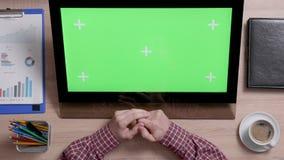 Las manos del hombre tocan la esquina izquierda superior de una pantalla verde en monitor del tacto almacen de metraje de vídeo