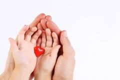 Las manos del hombre y del bebé que llevan a cabo un corazón rojo Fotos de archivo