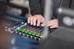 Las manos del ingeniero de sonido en la consola de mezcla fotos de archivo